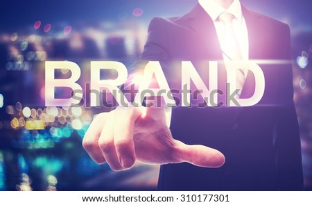 Businessman pointing at BRAND on blurred city background