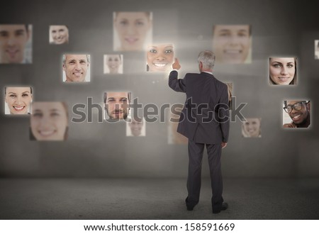 Businessman pointing at digital interface showing faces - stock photo