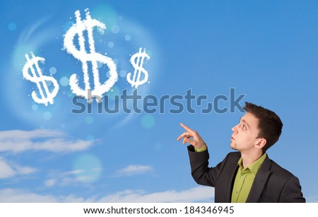 Businessman pointing at dollar sign clouds on blue sky concept - stock photo