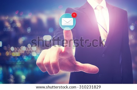 Businessman pointing at email icon on blurred city background - stock photo