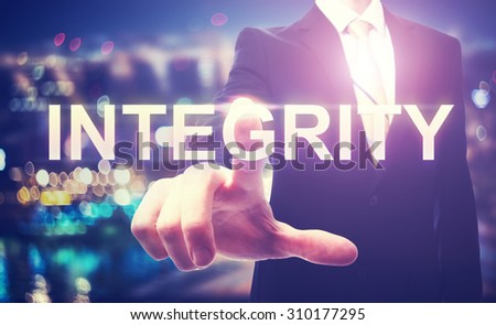 Businessman pointing at INTEGRITY on blurred city background - stock photo