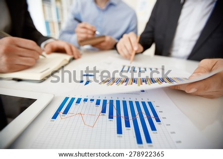 Businessman pointing at paper with chart during explanation