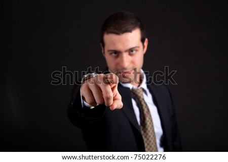 Businessman pointing at the camera on a dark background