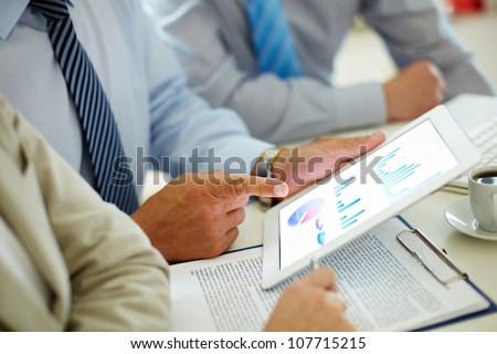 Businessman pointing at the screen of the touchpad with digital charts and graphs - stock photo