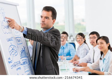 Businessman pointing at the whiteboard and explaining some idea to his coworkers - stock photo