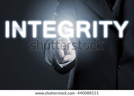 Businessman pointing at the word 'integrity' - business moral or ethics concept - stock photo