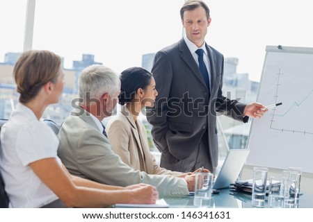 Businessman pointing at whiteboard during a meeting in front of attentive colleagues - stock photo