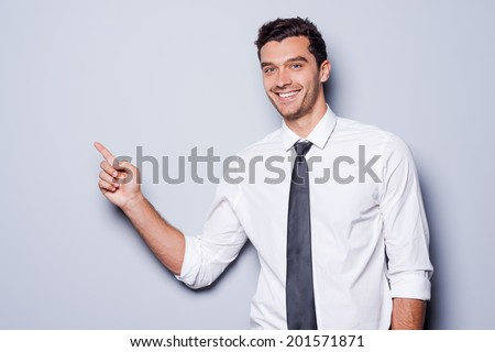 Businessman pointing copy space. Happy young man in shirt and tie looking at camera and smiling while standing against grey background and pointing copy space - stock photo