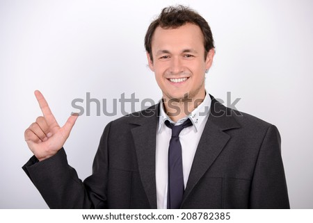 Businessman pointing copy space. Portrait of cheerful young man in formalwear pointing away and smiling while standing against grey background - stock photo
