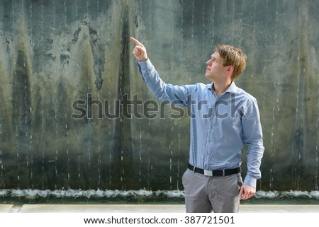 Businessman pointing finger outdoors