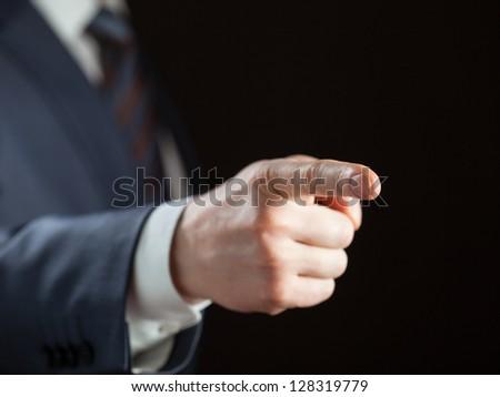 Businessman pointing forward on dark background - stock photo
