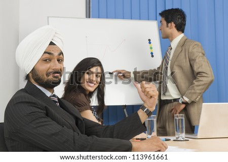 Businessman pointing on a flip chart in a conference room - stock photo