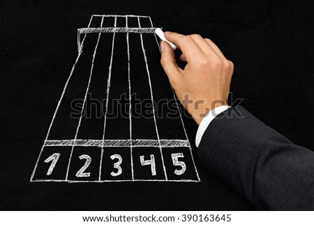 Businessman pointing on finish line of chalk drawing of a racetrack - goal, target reached or challenge concept - stock photo