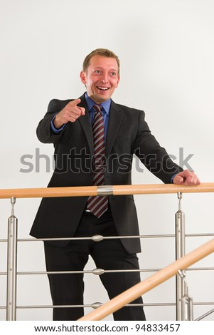 Businessman pointing something with the finger and smiling. - stock photo