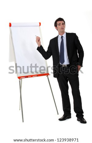 Businessman pointing to a flip chart - stock photo