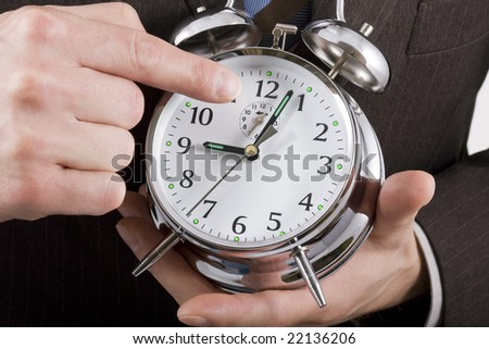 Businessman pointing to an alarm clock showing just past 9 o'clock