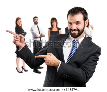 Businessman pointing to the side with many people behind