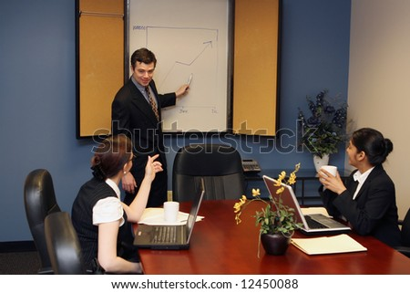 Businessman pointing to the whiteboard as he presents to two female colleagues during a meeting - stock photo