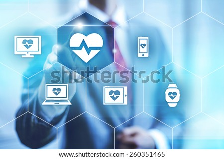 Businessman pointing towards camera selecting health application, virtual interface - stock photo