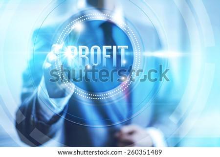 Businessman pointing towards camera selecting profit text, virtual interface - stock photo