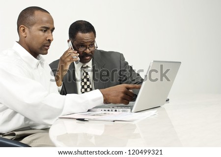 Businessman pointing towards laptop screen with colleague on call at desk in office - stock photo