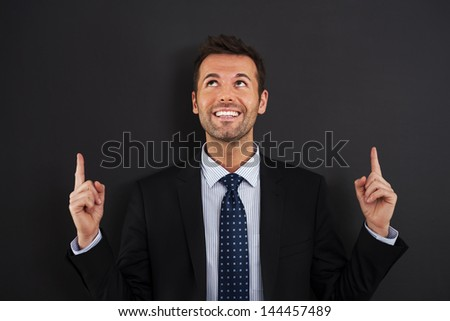 Businessman pointing up on copy space - stock photo