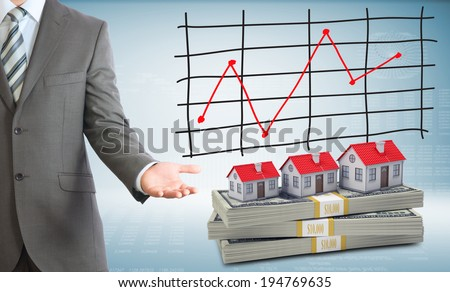 Businessman points hand on houses and packs dollars. Schedule of price increases in background - stock photo