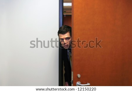 Businessman poking his head furtively through a doorway - stock photo