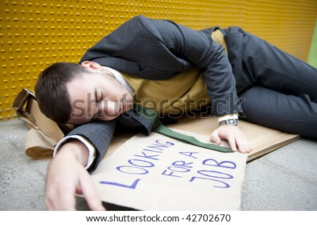 "Businessman portrait lying on street with ""Looking for a job"" sign. - stock photo"