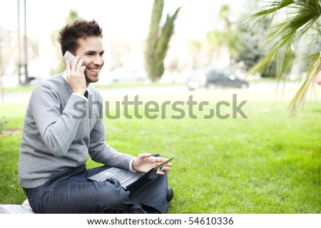 Businessman portrait using laptop and phone in park - stock photo