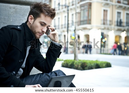 Businessman portrait with laptop and mobile phone - stock photo