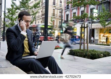 Businessman portrait with laptop and mobile phone in blurred urban background - stock photo
