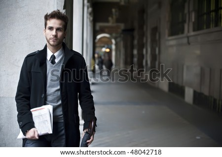 Businessman portrait with with newspaper and umbrella - stock photo