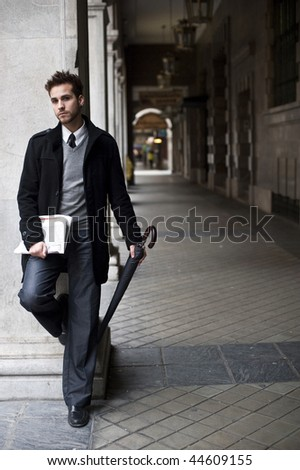 Businessman portrait with with newspaper and umbrella (piercing in ear)