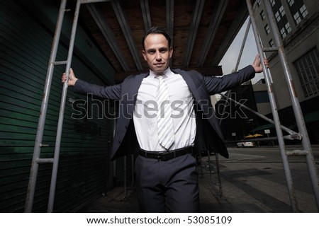 Businessman posing by construction scaffolding