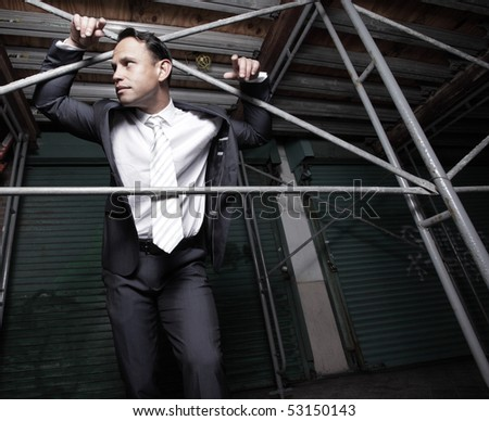 Businessman posing by scaffolding at night
