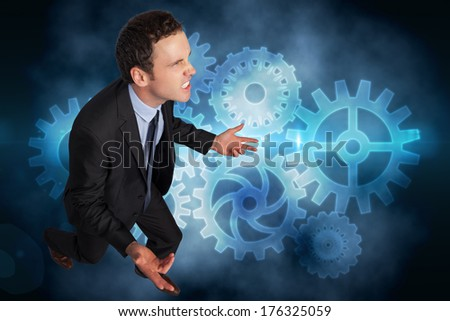 Businessman posing with arms out against cogs and wheels graphic