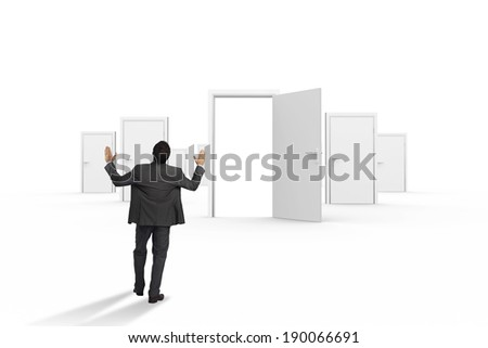 Businessman posing with arms raised against door opening revealing bright light