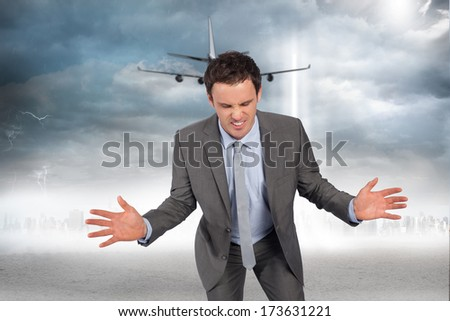 Businessman posing with hands out against city on the horizon with light beam