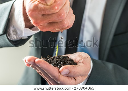 Businessman pouring water over a small green plant growing in fertile soil held in his cupped left hand, concept of ecology, environment and eco-friendly business, close-up.