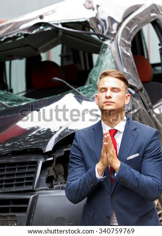 Businessman praying in front of his damaged vehicle - stock photo