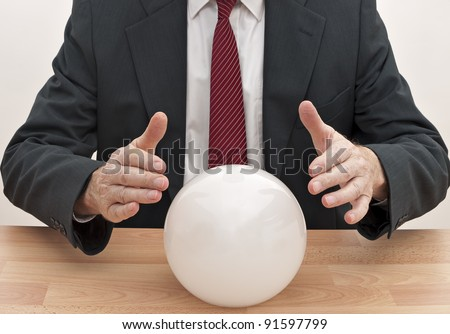 Businessman predicting future with crystal ball - stock photo