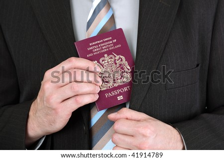 Businessman presenting a British passport at customs or check in area - stock photo