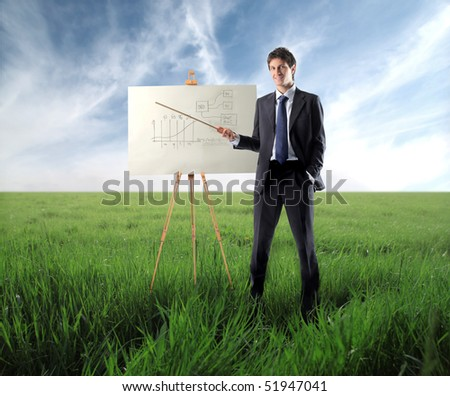 Businessman presenting a graphic on a green meadow - stock photo