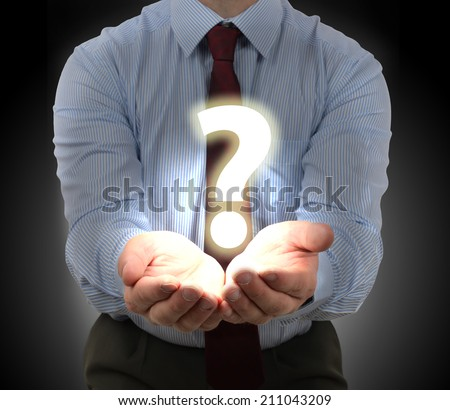 Businessman presenting a question mark glowing over hands - stock photo
