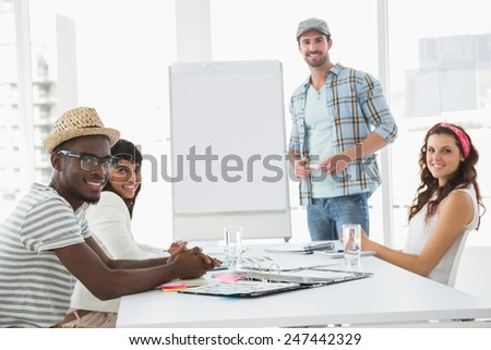 Businessman presenting and smiling colleagues listening in the office - stock photo