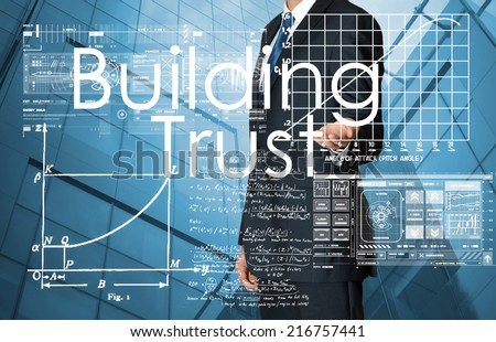 businessman presenting Building Trust text and graphs and diagrams with skyscraper in background - stock photo