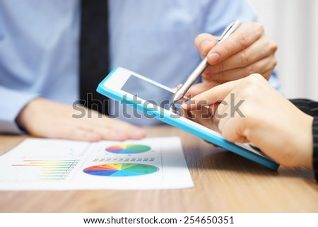 Businessman presenting document to client on tablet computer - stock photo