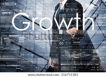 businessman presenting Growth text and drawing graphs and diagrams with skyscraper in background - stock photo