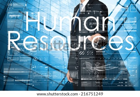 businessman presenting Human Resources text, graphs and diagrams with skyscraper in background, business concept - stock photo